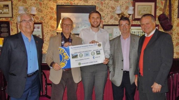 The photo shows, from left to right, Lion Keith Vear, Lion President Alvan Bailey handing the Lions cheque for £500 to Robert, then Lions Peter Oakley and Peter Crookes.