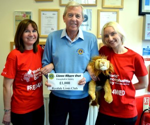 Encephalitis Society staff Julie Welburn (left) and Cassie Meegan-Vickers prepare for World Encephalitis Day with a £1,000 donation from Ryedale Lions Club fund-raiser Brian Johnson.