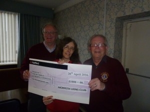 Kim Bibby-Wilson receiving a cheque from Lion President Ian Brown (right) with Lion Simon Pringle looking on.